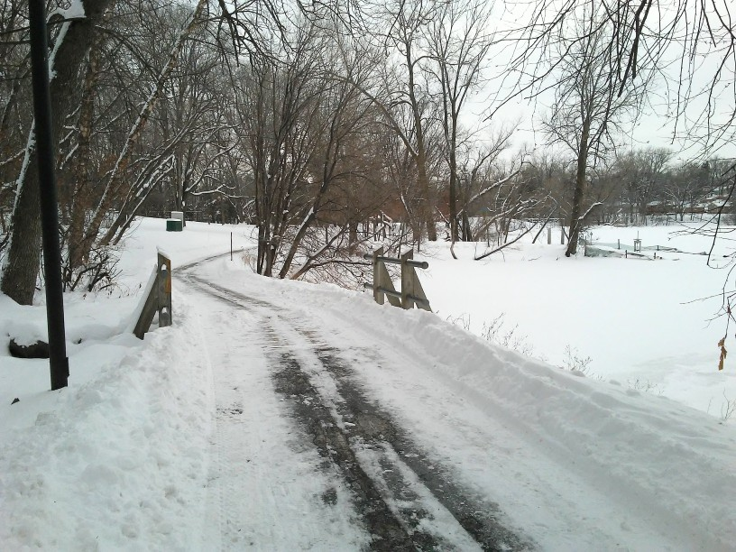 wooden bridge, snow, trees, a plowed road going over the bridge and a lake on the right side