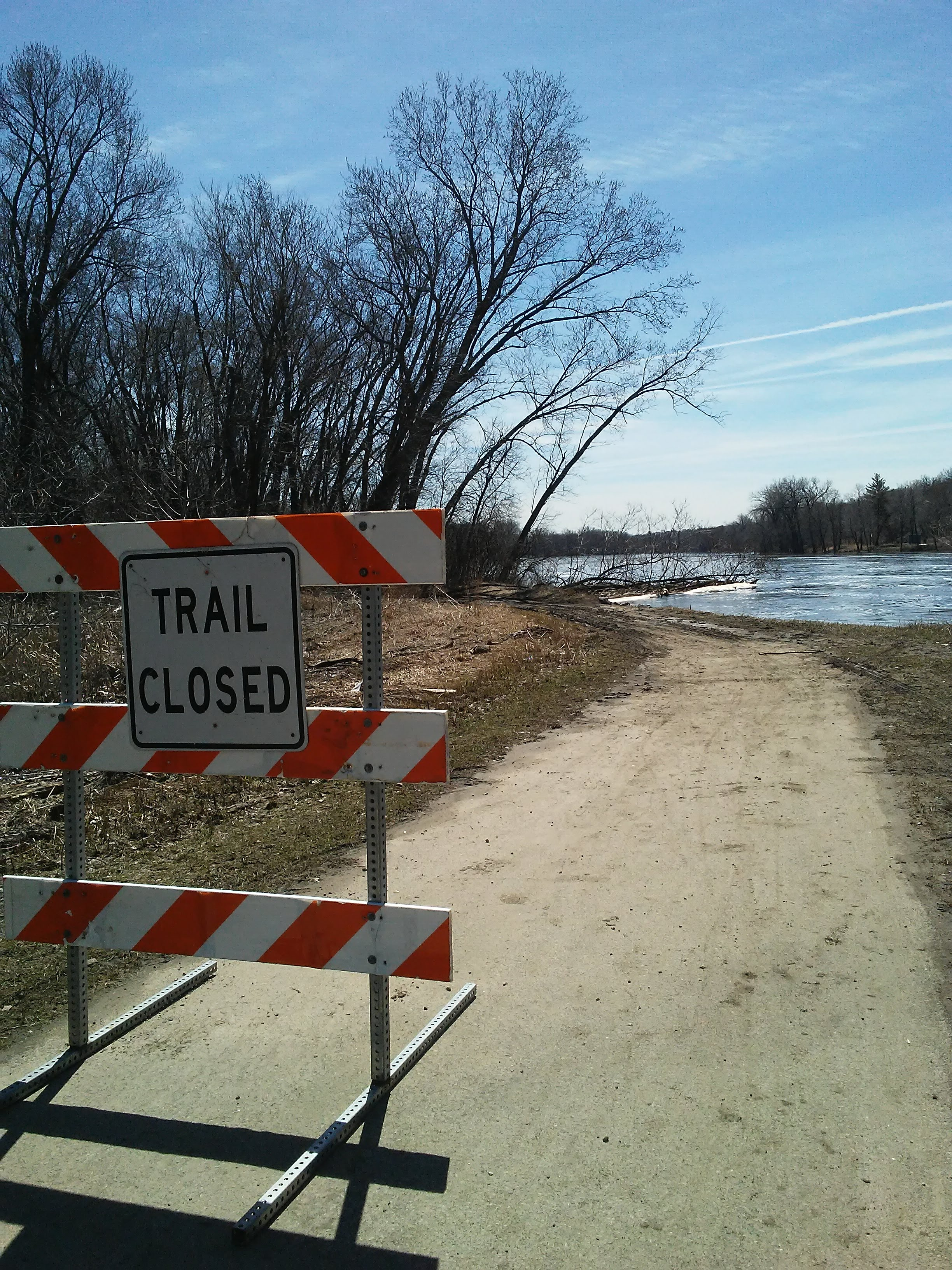 Trail closed sign and trail going to water