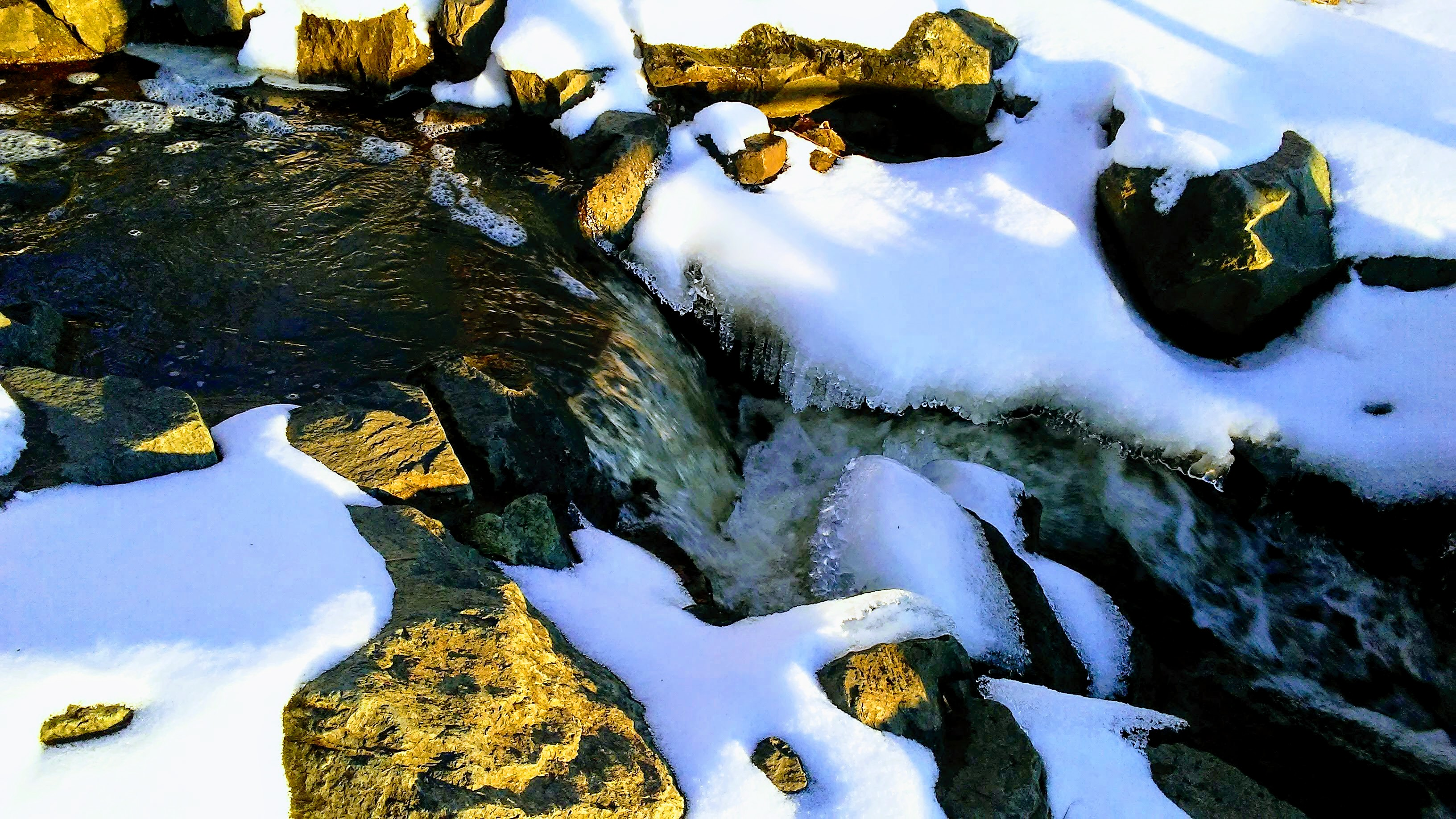 tan rocks, snow, water.