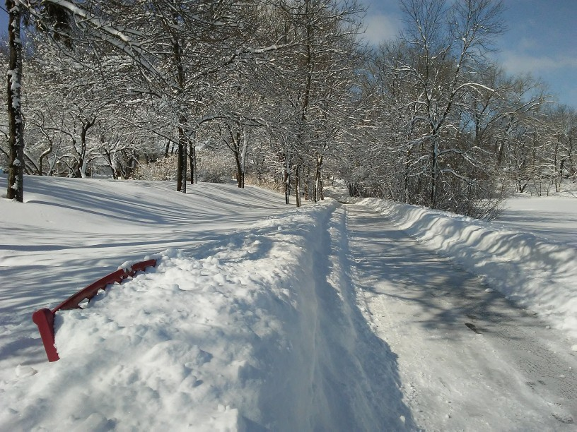 lots of snow cleared from a trail. almost covered red bench