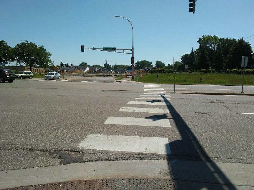 multi-lane pedestrian crossing, stoplight, a few cars