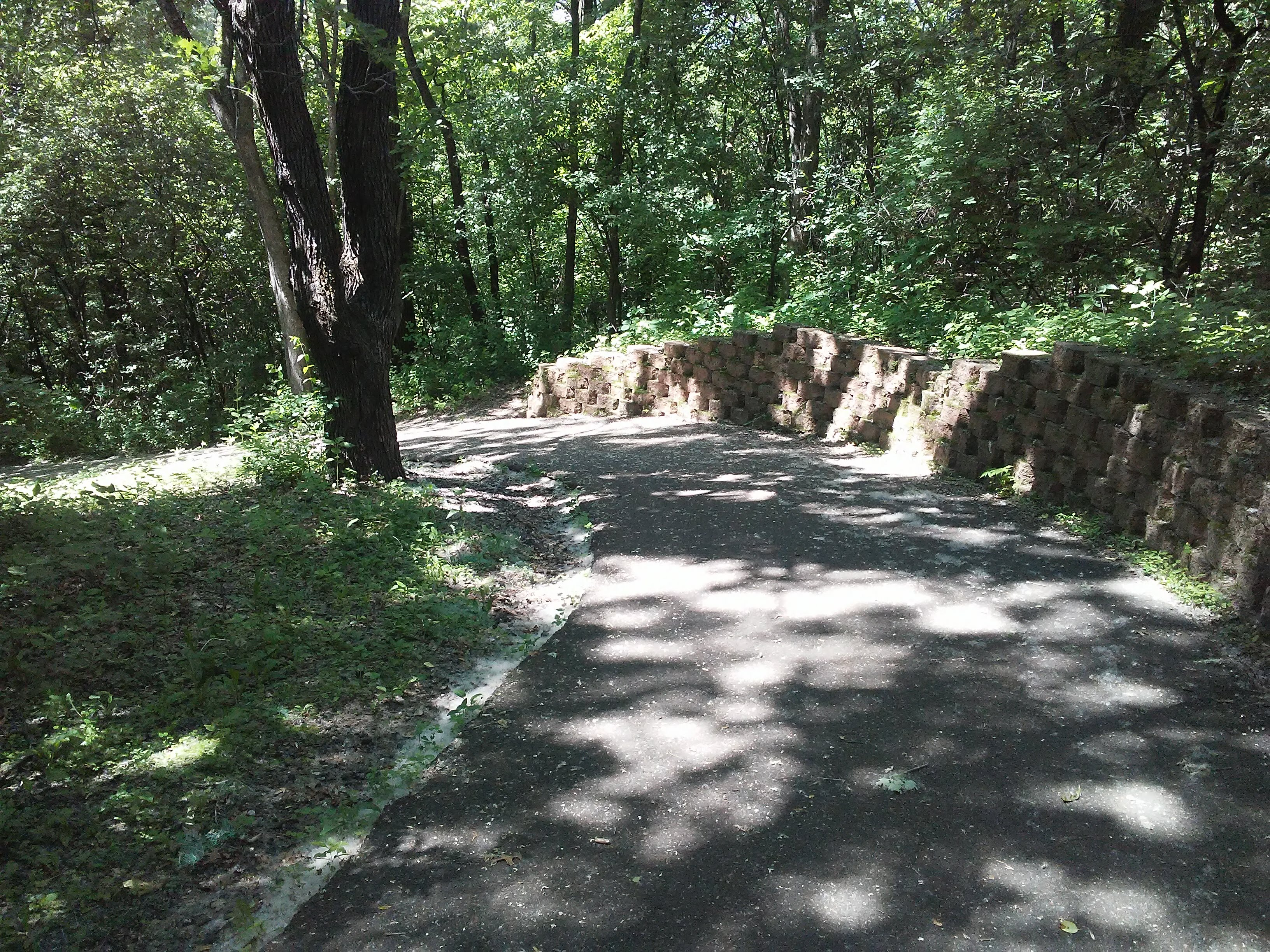 paved trail going downhill in woods, a brick retaining wall