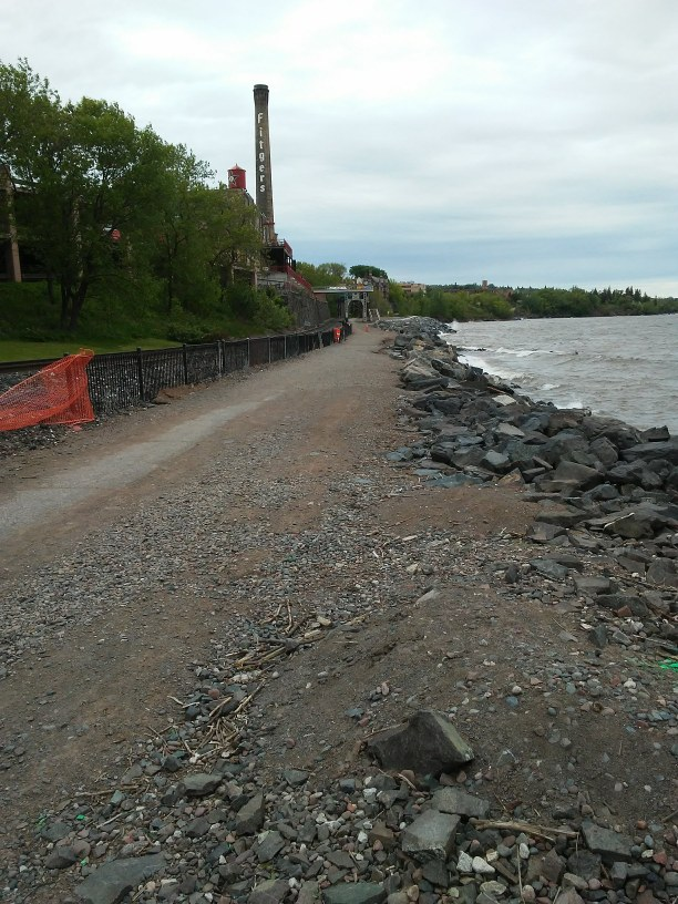 lakeshore path with rocks and the Fitger's tower and an orange construction fence
