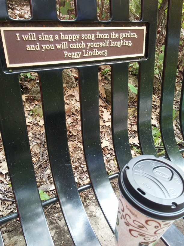 quote on a park bench and a coffee.