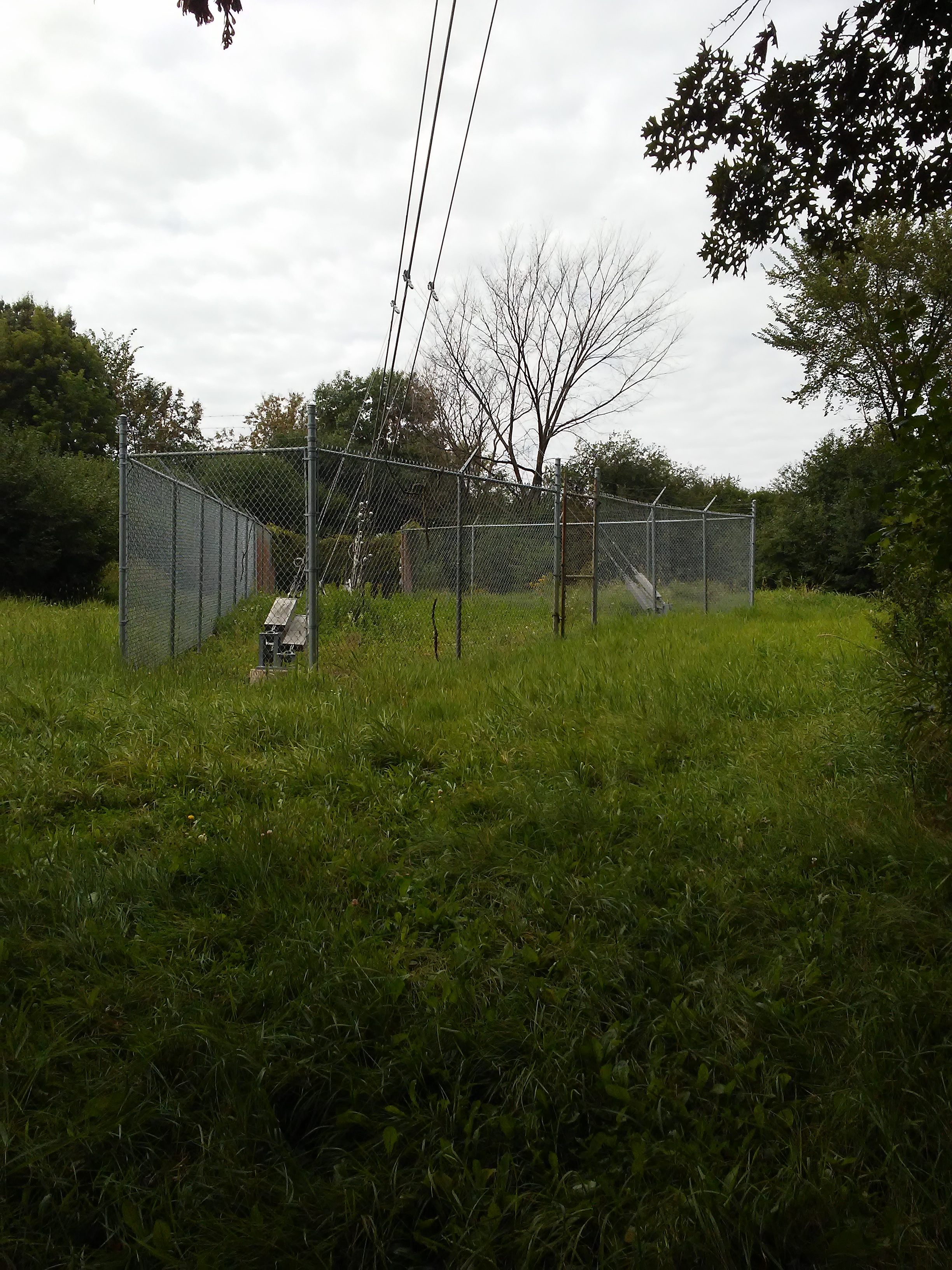 fenced in area with cables and grass in foreground