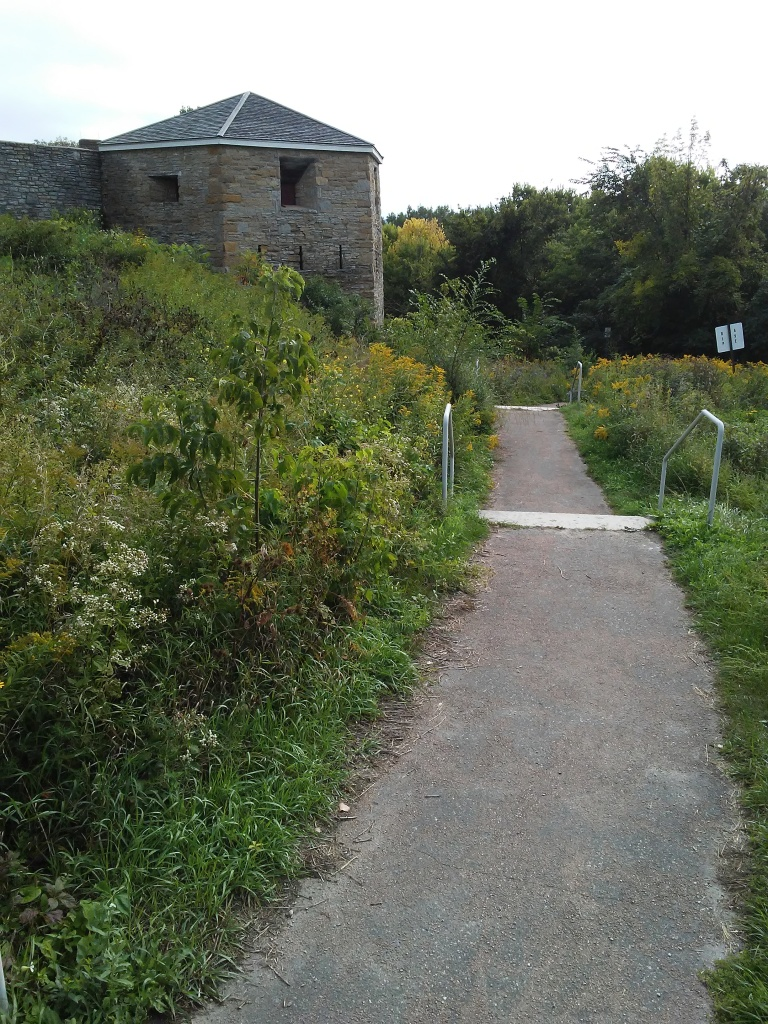 old stone fort and overgrown wild plants and a path