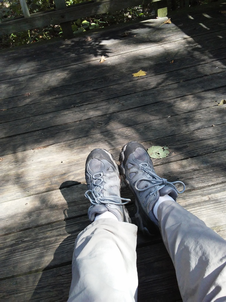 feet in grey athletic shoes on a wood deck.