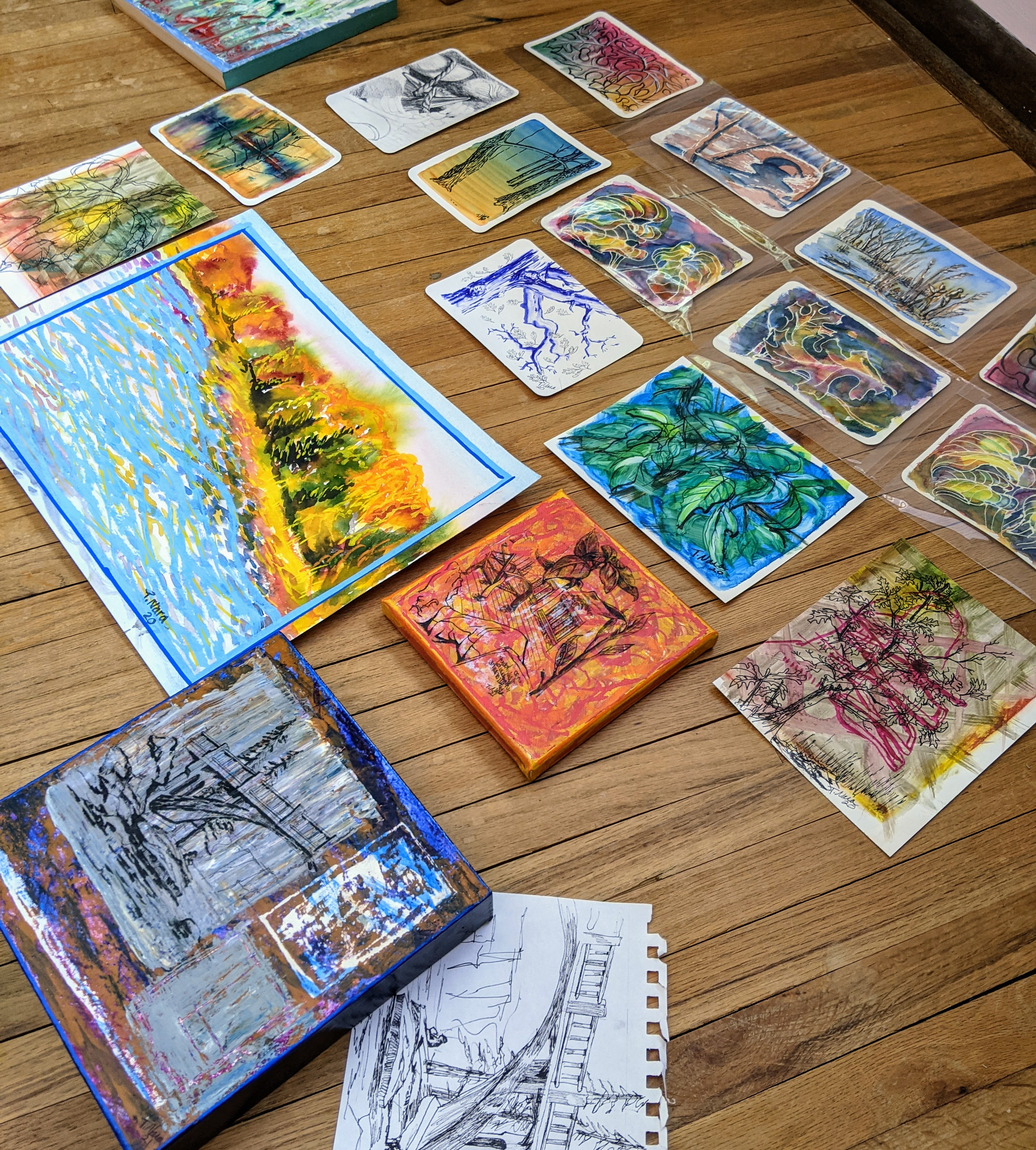 lots of paintings laid out on a wood floor